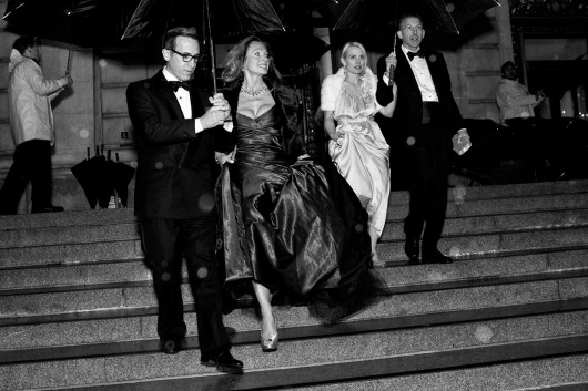 Alan Malouf (left) helps his friend Elisabeth Thieriot keep her gown dry while moving from dinner to the performance during a rainstorm at the San Francisco Ballet Opening Night Gala.