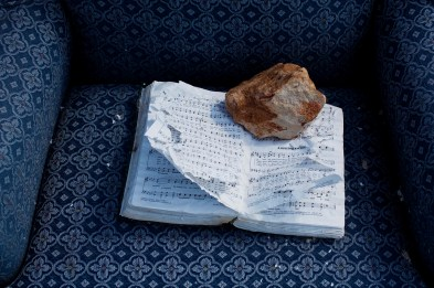 """A hymnal lays open to the song """"Amazing Grace"""" and is held open by a rock at the site where a church once stood in Joplin, Missouri on June 25, 2011. When the Joplin tornado of 2011 hit the town, a wall collapsed in the church, killing several congregants."""