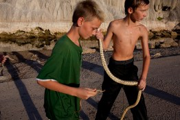 (L-R) Ryan Slagle, 10, (hand visible), Justin Kaitchuck, 10, and Kris Clark, 10, carry recently caught snakes near the river in Thermopolis, Wyoming on Sunday, August 21, 2011.