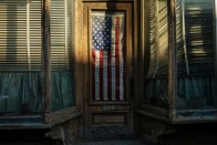 An American flag hangs in the doorway of an abandoned shop in the Williamsburg neighborhood of Brooklyn, New York on April 15, 2013.