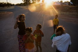 Children gather in the street at dusk, drawn outside by the cooler temperatures later in the day. It is not uncommon for midday temperatures in summer to hover over 40 degrees celsius (104 degrees farhenheit) for weeks at a time. David Maurice Smith/Oculi.