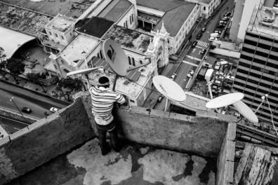 A man arranges the satellite dish, despite the poverty satellite TV is very common