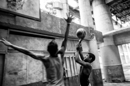 A man and a boy play basketball on a makeshift court on the ground floor of the tower when it was supposed to be the auditorium.