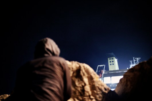 2012. Corinth, Greece. Migrant hide behind the rocks in the port during the night, waiting to attempt to illegally board a cargo ship going to Italy.