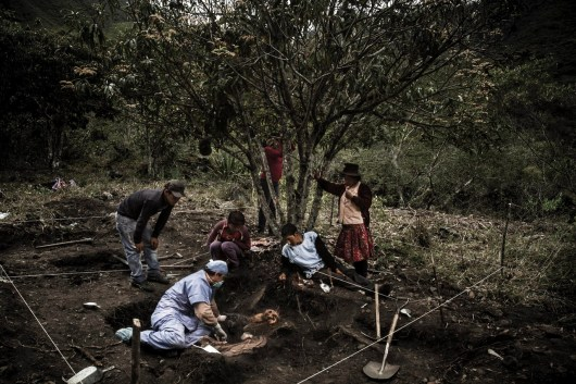 "Dannal Aramburu, forensic anthropologist (in blue), along with a family from Chungui observe the remains of two victims found in a mass grave of moderate depth, situated near a mango tree. This place is called Chaupimayu, within the area known as ""Dog's Ear"" in Chungui, and it's located at 800 kilometers from southeast Lima. The population is in charge of guiding the forensic teams. In order to reach this area, they have had to walk for 17 hours departing from the nearest highway. Chungui's people are concerned with finding their relatives, who died during violent times between 1980 and 1990. Between November and December of 2013, two forensic teams from the Public Prosecutor's Office exhumed approximately 50 mass graves in the long-suffering Chungi district, in Ayacucho, Peru. Shining Path and Peruvian Armed Forces are believed to have buried at least 200 people in these pits. During four weeks of work, 99 corpses were found. Chungui is a distant district located in the region of Ayacucho, which was –according to the Truth and Reconciliation Commission– one of the most affected Peruvian villages during the political violence and armed conflict time, between 1980 and 1995. Chungi's territory, of around 1000 square kilometers, was the scenario of multiple slaughters caused by both subversive organization Shining Path and Peruvian Policing Agencies (Army and Police forces). Currently, that same area contains 320 mass graves with the remains of more than 1,384 victims, waiting to be acknowledged by their families, mostly orphans and survivors of such harsh time. The Truth and Reconciliation Commission estimates that 1,384 people there died by assassination.  Today, most of Chungui's population lives in extreme poverty. They are part of VRAEM, a large area of valleys surrounding the rivers Ene and Apurimac that also account for the most extensive Peruvian territory dedicated to production of cocaine paste and coca. Although one part of Chungui di"