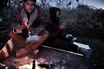 Khabir (left) and Zahir, illegal Afghan immigrants, sit at a fire while Zaher prays, Subotica, Serbia, Nov. 10, 2012. Zaher lost his legs below the knees. It was amputated due to freezing. He made it to Serbia on crotches and one proestetic leg. Zaher says he is 16 and Habir 15 years-old. The two have been traveling together from Greece. Many illegal immigrants try to get from Greece through the Balkans to northern parts of the European Union. Recently, Serbian police deported many refugees from here to Macedonia.
