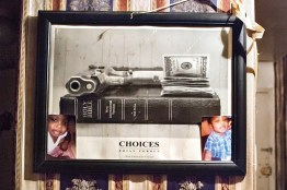 Gun, money, Bible and family in a frame hanging in defendantÕs living room. Bedford-Stuyvesant, Brooklyn, NYC, 2013.