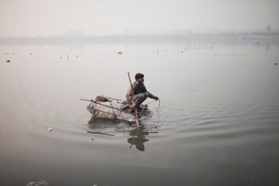 street boy fishes for coins using a string and a magnet along the Yamuna river in Delhi, the main affluent of the Ganges Feb 2014