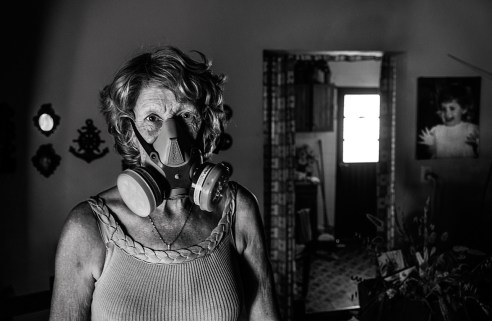 """11-18-2014, Libero, Province of Entre Ríos. Marta Elsa Cian (1947). Poultry farmer. In town, they call her """"the masked crazy woman"""" because every time she leaves her home she has to wear a protective mask to avoid inhaling the continuous drifts of agrotoxins sprayed in the vicinity of her house. In 2001, she suffered exposure to multiple agrochemicals employed in soybean and rice monoculture crop farming which affected her health causing chronic respiratory failure, hypertension, neuropathies combined with hematological and cardiologic symptoms."""