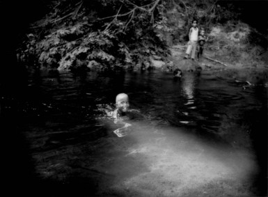 Batek Negrito boy swims in the pure waters of a stream that comes out of the old growth rainforest of Taman Negara National Park, a protected forest almost completely surrounded by oil palm plantations. Near Kuala Koh, Kelantan, Malaysia. Taman Negara National Park, 434,300 hectares (4,343 sq. km) of protected primary rainforest that supports tigers, sumatran rhinoceros, Asian elephants, Malaysian gaur (wild bovine), tapir, gibbons, monkeys totalling over 200 species of terrestrial animals, over 300 species of birds and over 1,000 species of butterfly. Malaysia's dwindling rainforests are home to over 14,500 species of flowering plants and trees. This is the homeland of the Batek Negrito people.