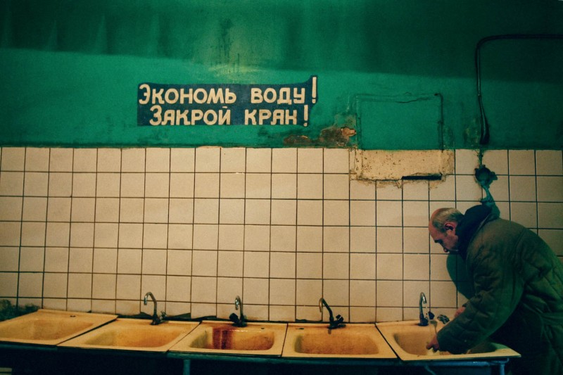 """An inmate washes his hands before dinner, under the sign """"Save the water, close the tap"""". Life in LTP is surrounded by signs, instructions, regulations and rules. Labour Treatment Profilactorium for alcohol addicted in Belarus. LTP is a part of the penal system and Belarus is the only country in the world that still practices the punishment of obligatory incarceration for addicts. There are 5 LTP in Belarus, about 1600 inmates each. One LTP is for women, the other ones are only male. The main treatment is labour, and camomile tea."""