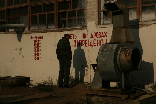 """An inmate stands in front of a wall, waiting for his obligatory work hours to pass, while the messages on the wall tell the exact times of allowed breaks and """"Forbidden to sit on wood"""". Labour Treatment Profilactorium for alcohol addicted in Belarus. LTP is a part of the penal system and Belarus is the only country in the world that still practices the punishment of obligatory incarceration for addicts. There are five LTP in Belarus, each housing about 1600 inmates. One LTP is for women, the others are all male. The main treatment is labour, and camomile tea."""