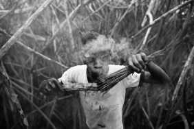 Jefferson Muñoz blows into a torch made out of coconut husks. The torches blow smoke for hours repelling the vicious mosquitoes and black flies of the mangrove. Insect repellent only repels insects for a few minutes after application. Cayapas Mataje Reserve, Ecuador. 2014.