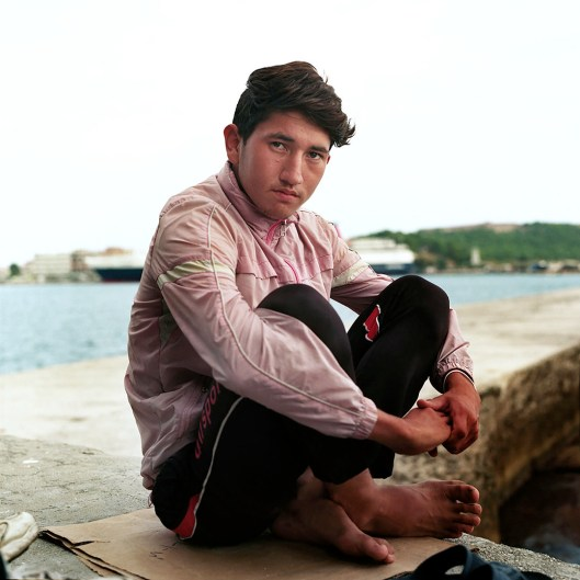 An Aghan boy sits by the harbour in Mytillini where he and his friends wait to get a ticket for the next ferry to Athens. When asked about his future dreams and visions he says: ' I left my home in Afghanistan where the Talibans make life so hard. When I come to Europe my dream is to become a football player and join Real Madrid.'