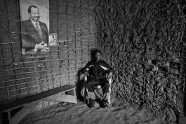 The baka pygmie chief of the village of Bosquet poses in his house next to a photo of the President of Cameroon, Paul Bija. Dja Faunal Reserve.