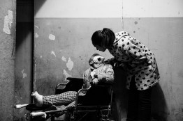 """Lucia Veneroso, 22 years old, kisses her daughter Martina, 5 years old. Martina is struggling, for 9 months, against bone sarcoma. The cancer has confined her to a wheelchair. After 9 cycles of chemotherapy, she's waiting for the autotrasplant. December, 16 2015 Casoria-Naples. Casoria is a small town in the so-called """"Land of fires"""", an area in Campania between the province of Caserta and the province of Naples, sadly re-known for being the most polluted area of this region due to millions of toxic waste that have been illegally dumped here over the past 20 years. The result of the illegal industrial dumping, hidden underneath various sites in Campania, is dioxin, tetrachloride, lead, arsenic, PCBs, asbestos, industrial sludge, toxic solvents, and other chemicals seeping into the soil and ground water. I met Lucia at her place. I asked her to tell me the story of her daughter Martina and to pose for me with her."""
