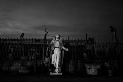 """Casalnuovo, Naples-Italy. The Virgin Mary statue in a street of Casalnuovo. Casalnuovo is one of the towns in the so-called """"Triangle of death"""" within the Land of fires, an area in Campania among the province of Caserta and the province of Naples, sadly re-known for being the most polluted area of this region due to millions of toxic waste that have been illegally dumped here over the past 20 years. National and international industries have been illegally disposing hazardous waste thanks to deals with local politicians and the Camorra, cutting down the enormous costs of legal disposing. The area is also interested by a worrying and wide rise of cases of cancer, especially among children and young people, though a direct connection between illegal landfills and illness has not been officially proved yet."""