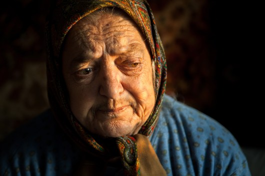 "Pasha, an elderly woman living in rural Moldova, sits in the warm evening sunlight, as we talk about her life in the single, small room she inhabits everyday. She is frequently moved to tears as we discuss her exile to Kazahkstan, ""[The night we were deported] Éthey took us to the police station in Floresti (a nearby town to Vadeni, PashaÕs home village, in the Northern region of Moldova). From there, they put us in a cattle car on a train. There was nothing inside. No toilet, no food, nothing, and thus we travelled for 2 months É some people died [during the journey], inside the train cars.Ó Ð Pasha Graur Across the former Soviet Union, millions of people were forcibly deported over the course of decades to the Eastern Soviet States of Kazakhstan and Siberia. This event is one of the longest and deadliest government campaigns in history. In Moldova, hundreds of thousands of people were deported over the course of two decades, from 1939 to the early 1950Õs. The wave of deportations targeted intellectuals, large landowners, dissidents and, at times, regular people who had done nothing to promote attack. Those who were deported had their land and homes taken from them and redistributed to the Soviet state and were deemed ÒEnemies of the PeopleÓ and were systematically shamed and silenced over the course of decades. Only recently has Moldova been willing to listen to the stories of deportees and try to understand the dark history of their country. PashaÕs memories, like many memories from deportees, regularly jump from the distant to the more recent as she tells me of the day that she requested her sister Ana Graur-Munteanu, along with her family, to take her in and let her be part of their family due to the lack of care she found with her in-laws in her old age, ÒMy daughter-in-law... Better not talk about her. Not even once did she take care for me and she never will. She once went to a neighbor to tell her that if I wasnÕt going to leave, she would pack my bags and kick me outÉ And so IÉ wrote a letter to Alex (Ana GraurÕs son) and Ludmilla Munteanu (Ana GraurÕs daughter-in-law, with whom Ana lives), to their children, to the relatives from Italy and to my sister and I wrote them, ÔPlease accept me into your family, please come and take me as soon as you can, for I have had enough, I can't take it any more! Other people have food to eat, but although I have money, I starve, for I can't go and buy what I need.Ó Pasha can no longer walk due to extreme leg pain and is confined to her one room in the small separate house she and Ana share. Pasha often thinks about her death saying, ÒI keep telling them to bury me next to our mother, for all my life I've been among strangers.Ó"