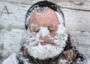 Local hunter washes his face with snow. To sustain good physical form and health (that is essential for a hunter) locals workout and ski. Rubbing snow on face and body is very comon, especually after workouts and banya (Russian sauna). Katangsky District, Irkutsky region. Russia, 2016