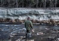 The hunter looks at a glacier at the beginning of June. Katangsky District, Irkutsky region. Russia, 2017