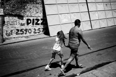 A girl looks over her shoulder while she walks in the middle of the street during a police raid in which 400 policemen surrounded Complexo do Alemão, where an estimated 70.000 people live. March 2007.