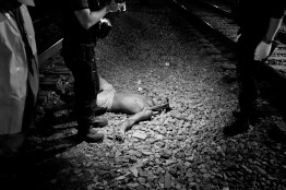Police officers from the Homicide Division investigate a crime scene where one man lays dead between train lines in Madureira in northern Rio de Janeiro, during the FIFA World Cup. July 2014.
