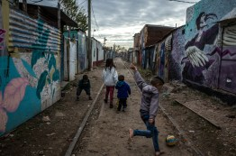 Buenos Aires, Isla Maciel. Children play football along the Pinzon, the main street of the Isla Maciel. Once it was a railway track who divided the original part of Isla Maciel from the new part, Dock Sur. It was the theather of many fights between the people who lived here. Now it is the poorest and the most dangeous part of the suburb.The first part of the street is controlled by the Paraguayan, the rest by the Argentinian. Drug deales are positioned on every corner.