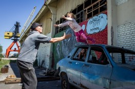 """Buenos Aires, Isla Maciel. Kids playing in the street. One girl jumps from one of the many burned stolen cars abandoned along the street. Behind her on a wall it is written """"Poverty or??? mhmm""""."""
