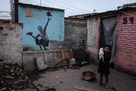 Buenos Aires, Isla Maciel. A little girl plays with her dog in front of the house where she lives with her mother M., her aunt and 8 among brothers, sisters and cousins. Her mother, who is addict and prostitutes herself, and two sisters have recently been diagnosed with syphilis.