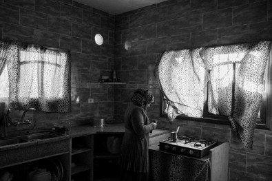 Azmi Qudiah's wife is seen making coffee in their damaged home in Khuza'a, Khan Younis, southern Gaza, on Nov. 2nd 2014. Their family house was damaged for the 7th time. During the war, they evacuated to Khan Younis and upon return, found that their rabbits, chicken and sheep have been killed and their land was bulldozed. - they're only left with 10 pigeons. Because most of the rooms a rubbled and completely damaged, they rented a house, so they can live together again.