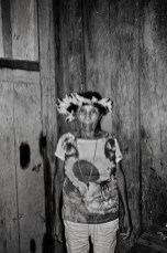 "PANORAMA, BRAZIL - OCTOBER 17, 2017: Katisiká Karipuna portrayed inside her house in the Panorama village. She is one of the four tribespeople who still speaks the Karipuna language. The majority of the tribe was wiped out by diseases following contact with Amazon settlers in the 1970's, during Brazil's military governments' drive to occupy the Amazon. Today the Karipuna population number 40 memebers. The Karipuna Indigenous territory in Brazil's North-western state of Rondonia sits on the so called ""arc of deforestation,"" the agricultural frontier advancing into the Amazon forest and one of the front lines of the country's deadly conflict over land and resources. Since 2015, the land has been increasingly targeted by loggers and land grabbers but the tribesmen so far say their complaints have fallen on deaf ears. In Rondonia, death threats are serious. The state consistently tops the list of land conflict killings, with 15 already in 2017, according to watchdog group Comissão Pastoral da Terra."