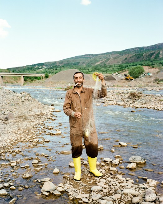 A fisherman is fishing long the stream of a tributary river to the Euphrates across a cement factory.Turkey