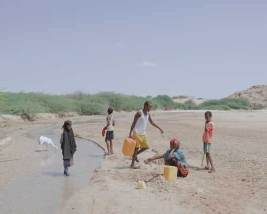 Nomads at an oasis near Biyo-Guure southeast of the port city of Berbera. Muna (11) and Mohamed (12), left in the picture, lead the 50 goats of their family every day to this small creed. In the aridity of the last years the creek dried up, 50 of their goats died. Approximately half of the inhabitants of Somaliland live as nomads outside the towns and villages, the livestock is their most important living basis. The continuing droughts of recent years have killed about 70 percent of Somaliland's livestock and forced tens of thousands of families to flee to the cities' IDP camps. Climate change has led to temperature changes in the Indian Ocean, pushing the wind and humid air that usually brings rain away from the mainland. The effects of climate change are increasingly affecting the entire Horn of Africa, leading to water scarcity, starvation and flight.