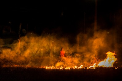 A person burning grass near his house in the community of Chilapa in the mountain region. This region has declared itself in crisis due to violence, disappearances and forced displacement due to organized crime and lack of rule of law. Guerrero, Mexico 2018.