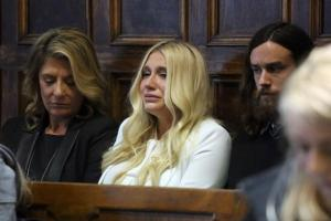 Kesha (c.) cries as she learns she will not be released from her record label contract in Manhattan Supreme Court Friday. Kesha's contract requires her to record six more albums for Sony Records.
