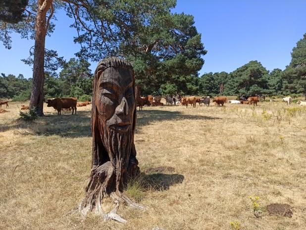 Busto rodeado de ganado