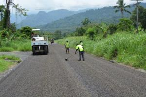 Soft tyre roller and road crew completing the sealing of one of Arawa's town roads.