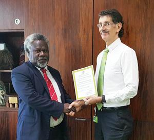 Reserve Bank of Vanuatu Governor Simeon Athy hands over the license for BSP Vanuatu Ltd to BSP Group CEO Robin Fleming. Credit: BSP
