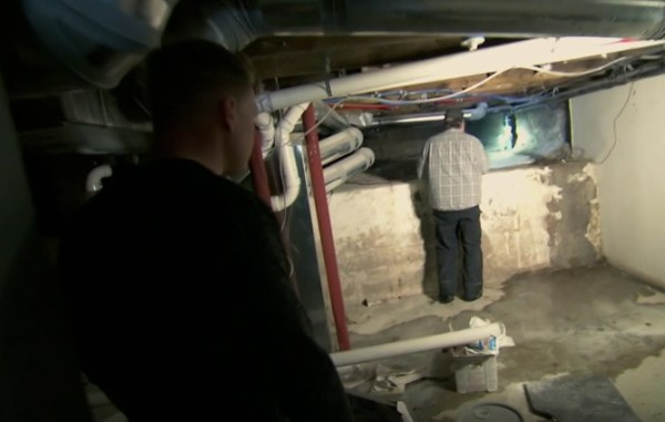 Nylund and a plumber assessing water damage on the episode. (DIY Network)