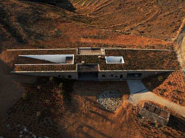 This house on the Greek island of Antiparos sits right where two slopes meet. Two long stone walls bridge the hills, allowing the house to naturally blend in the space.