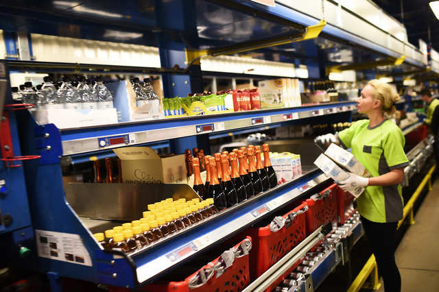 When a customer orders groceries through Ocado's site, human workers pick food off shelves along a 330-foot aisle. They then place them into the bins ...