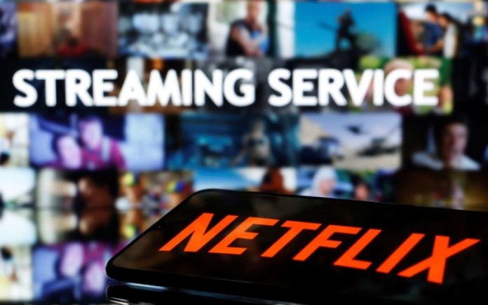© Reuters. A smartphone with the Netflix logo lies in front of displayed