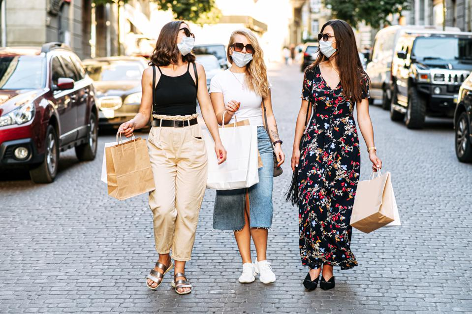 Three female friends in masks walk after shopping
