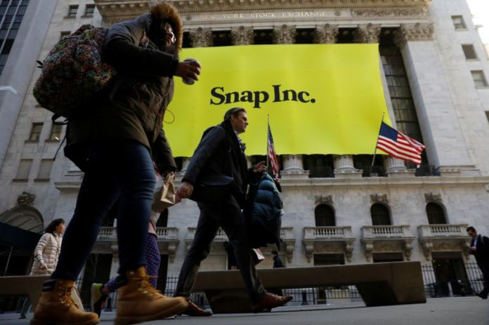 © Reuters. Pedestrians walk past the front of the New York Stock Exchange (NYSE) with a Snap Inc. logo hung on the front of it shortly before the company's IPO in New York