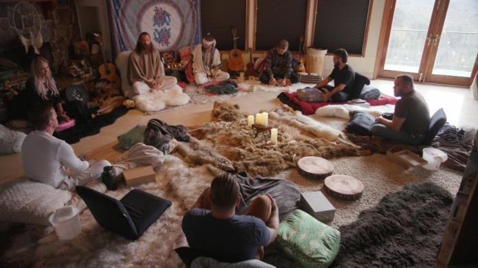 People are seated in a circle on the floor as part of a plant medicine ceremony.