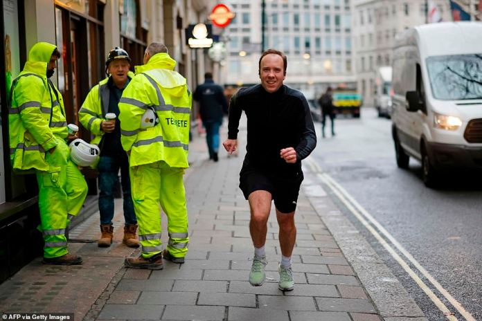 Health Secretary Matt Hancock poses running past photographers whilst out for a morning jog in Westminster today