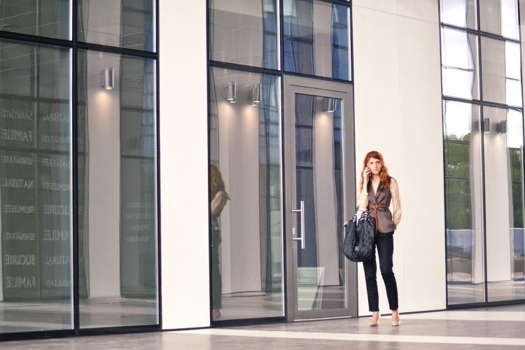 A woman in front of the office entrance.