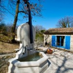 Limestone fountain with cello.