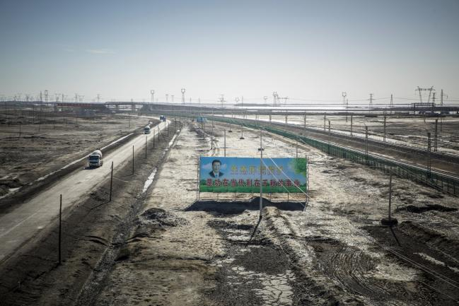 © Bloomberg. A billboard featuring Chinese President Xi Jinping and promoting environmental protection stands among power lines carrying electricity from the Golmud Solar Park on the outskirts of Golmud, Qinghai province, China, on Wednesday, July 25, 2018. Amid rising fears about a trade war, China's policy makers have unveiled measures to boost infrastructure construction and credit to smaller firms, as well as tax cuts. Photographer: Qilai Shen/Bloomberg