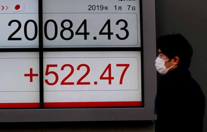 © Reuters. FILE PHOTO: A man glances at an electronic board showing the Nikkei stock index outside a brokerage in Tokyo